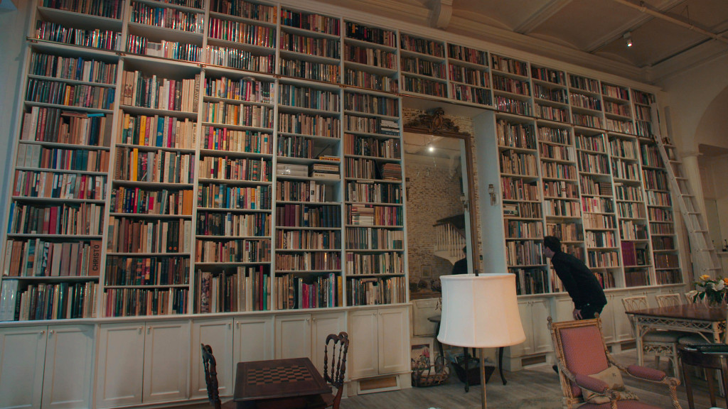 Adam Weinberger examining a bookshelf - THE BOOKSELLERS - Courtesy of Greenwich Entertainment
